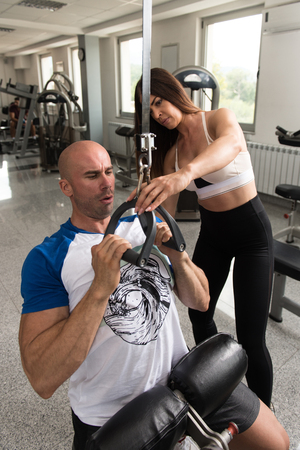 Young Man Working Out In Gym - Doing Back Exercise On Machine With Help Of Her Trainer Stock fotó