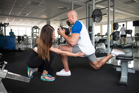 Strong Couple In The Gym And Exercising Quadriceps And Glutes With Dumbbell - Muscular Athletic Female and Male Fitness Model Exercise Stock Photo