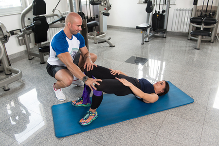 Attractive Couple Exercising With A Resistance Band In Gym As Part Of Fitness Bodybuilding Training