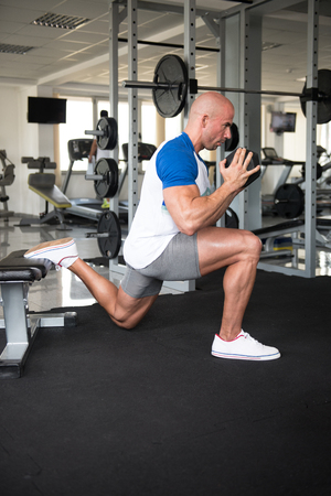 Strong Man In The Gym Exercising Legs With Dumbbells - Muscular Athletic Bodybuilder Fitness Model Exercise