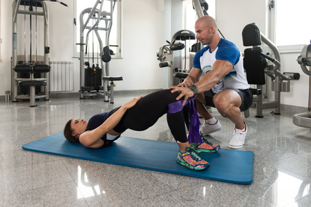 Couple Athlete in Sport Sportswear Workout With Elastic Resistance Band - Doing Legs Exercises in Gym