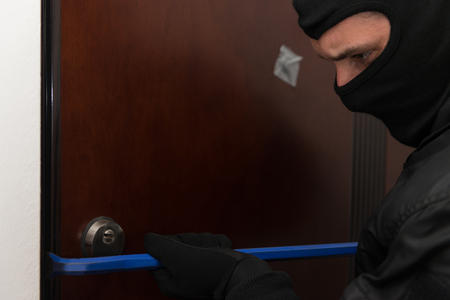 Man With A Black Mask Is Breaking Into A Home Stock Photo