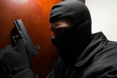 Man With A Black Mask And Gun Is Breaking Into A Home - Standing Behind The Door