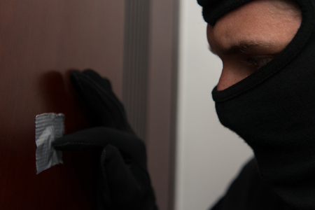 Burglar Breaks Into A Residential Building And Thief In The Mask Covers Peep Hole Stock Photo
