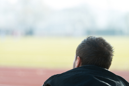 Back View of Young Man Sitting on Seat or Bleachers Sports Tribune and Support His Favourite Team Imagens
