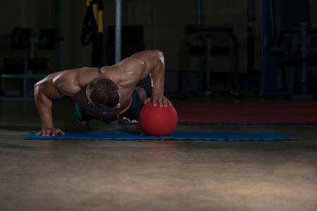 Young Adult Athlete Doing Push Ups On Medicine Ball As Part Of Bodybuilding Training