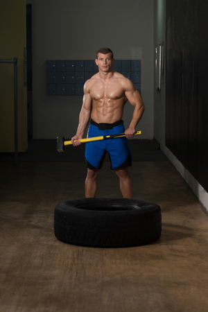Athletic Man Hits Tire - Workout At Gym With Hammer And Tractor Tire Foto de archivo