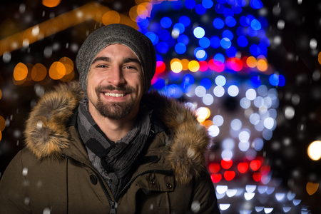 Having Fun at a Christmas Fairy - Young Cheerful Man Dressed Warm Is Standing In Holiday Market Stock Photo