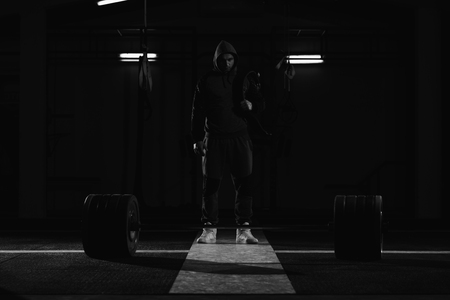 Powerlifter Stands in Front of the Barbel and Preparing for Deadlift