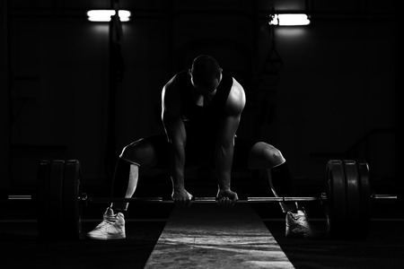 Professional Athlete Bent Over the Barbell and Is Preparing to Lift a Very Heavy Weight Stock Photo