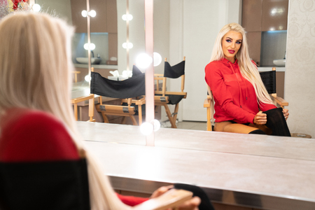 Fitness Woman in a Beauty Salon Looks at Her Reflection in the Mirror With Lamps