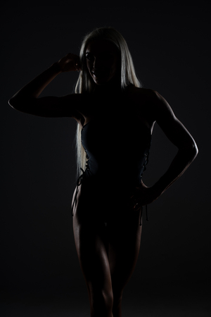 Silhouette Healthy Young Woman Posing in Studio - Isolated on Black Background