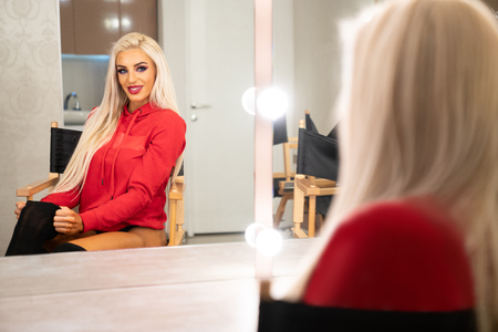 Beautiful Young Woman Looking at Her Reflection in a Dressing Room Mirror Stock Photo