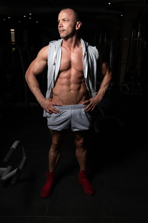 Portrait Of A Young Physically Fit Man Showing His Well Trained Body - Muscular Athletic Bodybuilder Fitness Model Posing After Exercises Standard-Bild
