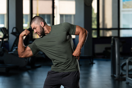 Young Muscular Man In Shorts And Green T-shirt Posing In Fitness Center
