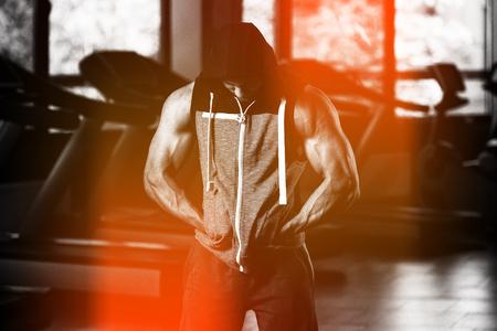 Ritratto di un uomo muscoloso in felpa con cappuccio in posa in palestra
