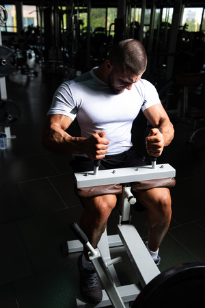 Athlete Working Out Calves On Machine In Fitness Center