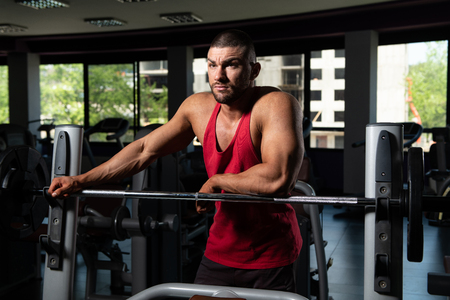Muscular Man Relaxing In Gym After Exercise Stock Photo