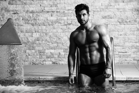 Young Healthy Good Looking Macho Man Model Athlete At Hotel Indoor Pool Stock Photo