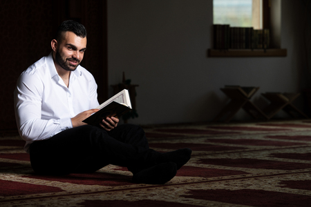 Attractive Muslim Is Reading The Koran Making Traditional Prayer to God Allah in the Mosque Banco de Imagens - 122162584