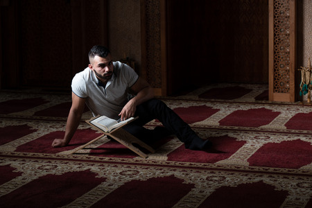 Attractive Muslim Is Reading The Koran Making Traditional Prayer to God Allah in the Mosque