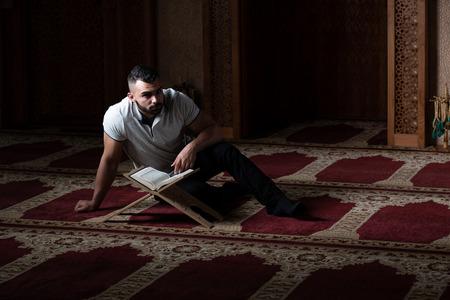 Attraente musulmano sta leggendo il Corano facendo la tradizionale preghiera a Dio Allah nella moschea