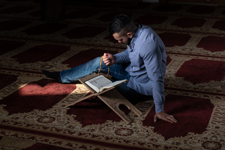 Attractive Muslim Is Reading The Koran Making Traditional Prayer to God Allah in the Mosque Banco de Imagens - 122244476