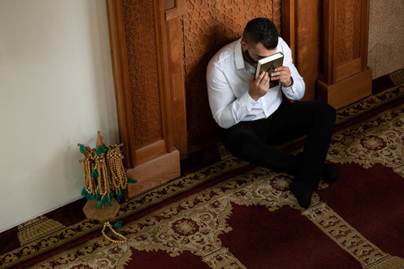 Businessman Muslim Is Kissing The Koran Making Traditional Prayer to God Allah in the Mosque