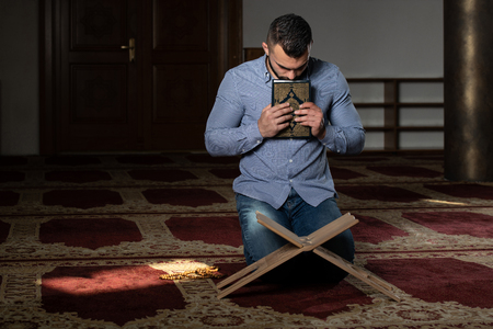 Businessman Muslim Is Kissing The Koran Making Traditional Prayer to God Allah in the Mosque Stockfoto