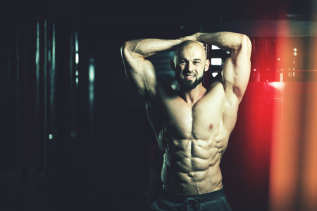 Handsome Young Man Standing Strong In The Gym And Flexing Muscles - Muscular Athletic Bodybuilder Fitness Model Posing After Exercises Stock Photo