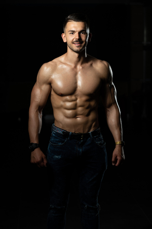 Handsome Young Man In Jeans Standing Strong In The Gym And Flexing Muscles - Muscular Athletic Bodybuilder Fitness Model Posing After Exercises