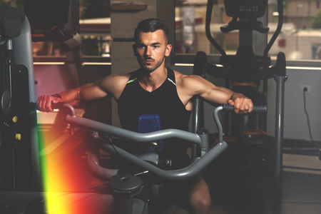 Handsome Athlete Doing Heavy Weight Exercise For Back On Machine Stock Photo