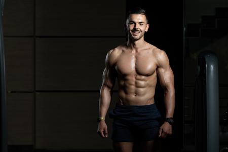 Retrato de un hombre joven físicamente en forma mostrando su cuerpo bien entrenado - Muscular atlético culturista Fitness modelo posando después de los ejercicios
