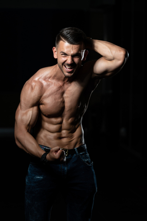 Healthy Young Man In Jeans Standing Strong In The Gym And Flexing Muscles - Muscular Athletic Bodybuilder Fitness Model Posing After Exercises