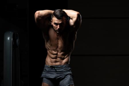 Porträt eines jungen physikalisch geeigneten Mannes, der seinen gut ausgebildeten Körper - muskulöses athletisches Bodybuilder-Eignungs-Modell Posing After Exercises zeigt Standard-Bild