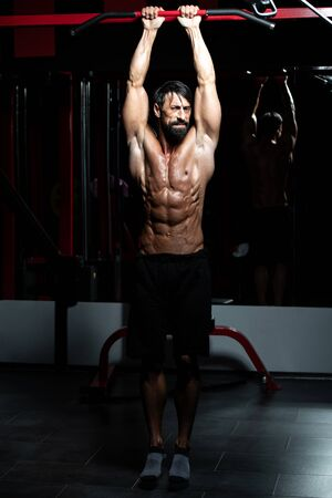 Muscular Middle Age Man Exercising Abdominals In Modern Fitness Center