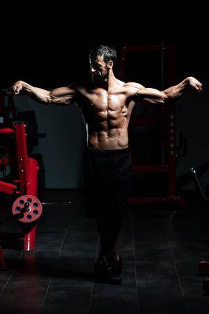 Porträt eines erwachsenen körperlich fitten Mannes, der seinen gut trainierten Körper zeigt - muskulöser athletischer Bodybuilder Fitness-Modell posiert nach den Übungen Exercise Standard-Bild