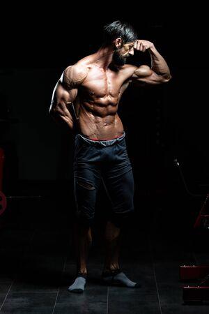 Porträt eines erwachsenen körperlich fitten Mannes, der seinen gut trainierten Körper zeigt - muskulöser athletischer Bodybuilder Fitness-Modell posiert nach den Übungen Exercise