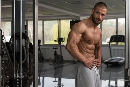 Young Man Standing Strong In The Gym And Flexing Muscles - Muscular Athletic Bodybuilder Fitness Model Posing After Exercises Stock fotó