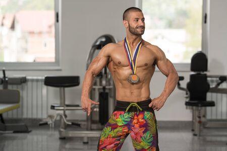 Bodybuilder Competitor Showing His Winning Medal - Male Fitness Competitor Showing His Winning Medal Stock fotó