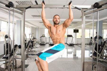 Man Performing Hanging Leg Raises Exercise - One Of The Most Effective Ab Exercises Stock fotó
