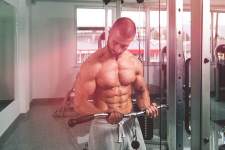 Muscular Fitness Bodybuilder Doing Heavy Weight Exercise For Biceps On Machine With Cable In The Gym