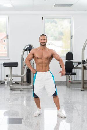 Porträt eines jungen physikalisch geeigneten Mannes, der seinen gut ausgebildeten Körper - muskulöses athletisches Bodybuilder-Eignungs-Modell Posing After Exercises zeigt