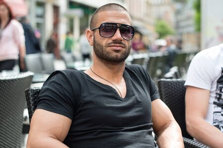 Portrait of Young Bearded Man With Sunglasses Serious Expression Listening With Attentive Sitting on an Outdoors Bar