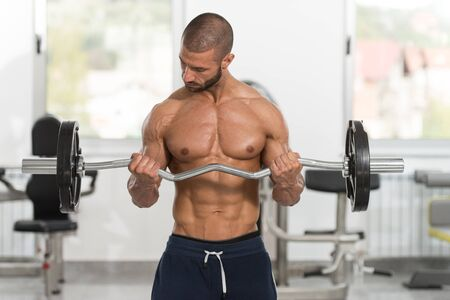 Muscular Man Doing Heavy Weight Exercise For Biceps With Barbell In Gym Stock fotó