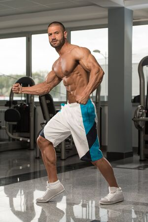 Handsome Young Man Standing Strong In The Gym And Flexing Muscles - Muscular Athletic Bodybuilder Fitness Model Posing After Exercises Stock fotó