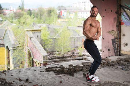 Porträt eines jungen körperlich fitten Mannes, der seinen gut trainierten Körper zeigt - muskulöser athletischer Bodybuilder Fitness-Modell posiert nach Übungen im Freien Standard-Bild