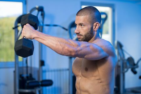 Man Working Out Shoulders In A Gym - Dumbbell Concentration Curls