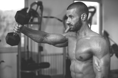 Athlete Working Out Shoulders In A Gym - Dumbbell Concentration Curls