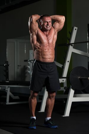 Handsome Mature Man Standing Strong In The Gym And Flexing Muscles - Muscular Athletic Bodybuilder Fitness Male Posing After Exercises